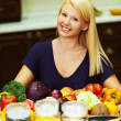 A portrait of blonde at kitchen table littered with products - Stockfoto