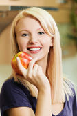 Blonde is holding an apple — Stock Photo