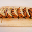 Sliced ​​loaf on wooden board - Stock Photo