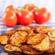 Still Life: fried fritters and tomatoes checkered tablecloths on — Stock Photo