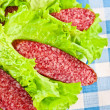 Stock Photo: Slices of salami wrapped in lettuce leaves
