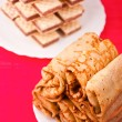 Feast of pancakes and waffles on red tablecloth — Stockfoto