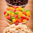 Cashew nuts, candied peanuts and chocolate on bamboo table cloth - Foto Stock