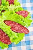 Slices of salami wrapped in lettuce leaves — Stock Photo