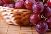 Still Life: wicker basket with grapes in braided — Stock Photo