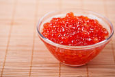 Red caviar in bamboo table cloth — Stock Photo