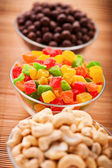 Cashew nuts, candied peanuts and chocolate on bamboo table cloth — Stock Photo