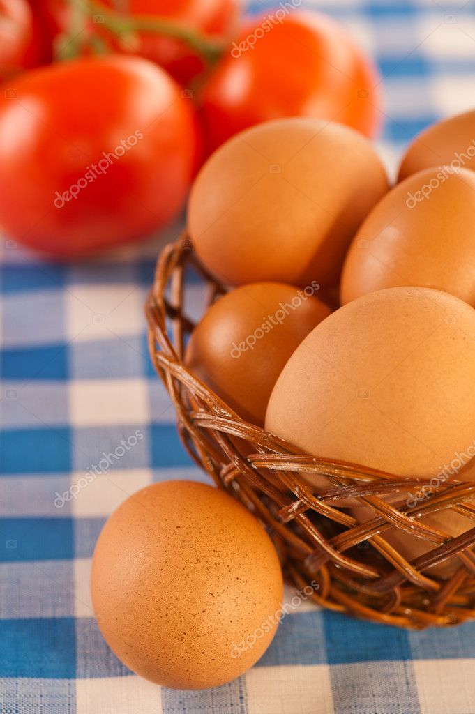 Close-up beige incubator eggs in wicker vase and red tomatoes on blue and white checkered oilcloth tablecloths — Stock Photo #7826104