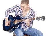 Young handsome man with blue guitar over white — Stock Photo