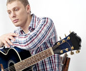 Young handsome man with blue guitar — Stock Photo