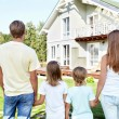 Family with children looking at the house — Stock Photo