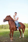 Little girl with father on a horse — Stock Photo