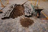 Stones, a wheelbarrow, and tools for paving — Stock Photo
