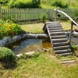 Small garden pond with wooden bridge — Stock Photo
