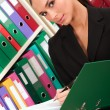 Business woman in front of shelves with folders — Stock Photo
