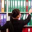 Business woman in front of shelves with folders — Stok fotoğraf