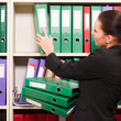 Business woman in front of shelves with folders — Foto Stock