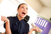 Business woman screaming in telephone receiver — Stock Photo
