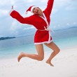 Young woman on the beach in santa's costume — Stock Photo