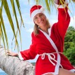 Young woman on the beach in santa's costume siting on the palm — Stock Photo