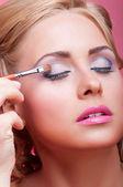 年轻女子应用化妆品油漆刷 — 图库照片