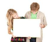 Couple holding blank billboard — Stock Photo