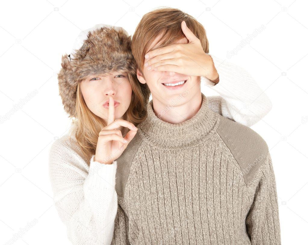 Girl in winter hat covering her boyfriend's eyes to surprised him and gesture silent — Stock Photo #6837092