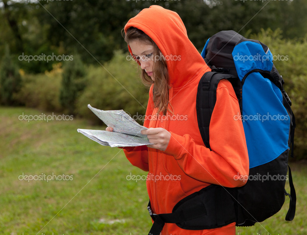 A beautiful caucasian young woman with map in her hands, rucksack on her back standing in a park outdoors in windy day on vacation — Stock Photo #6838564