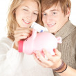Couple putting five euro in piggy bank — Stock Photo