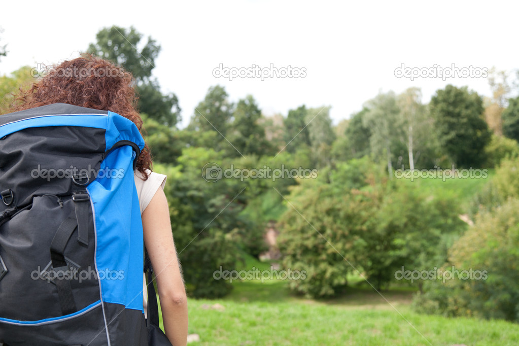 Traveller - young woman hiker with blue backpack looking away — Stock Photo #6915547