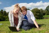 Teenage couple using laptop — Stock Photo