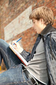 Male student learning near the wall — Stock Photo