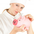 Cook woman with piggy bank - Stock Photo