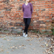 Girl leaning against brick wall — Stock Photo