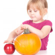 Little girl with pumpkin and apple — Stock Photo