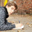 Male student learning by the wall — Stock Photo