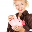 Royalty-Free Stock Photo: Girl putting five euro in piggy bank