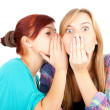 Girl whispering in friends ear — Stock Photo