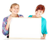 Female friends holding blank sign — Stock Photo