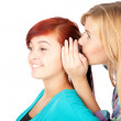Girl whispering in friends ear - Lizenzfreies Foto
