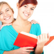 Female friends reading book — Stockfoto