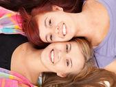 Girl friends lying head to head — Stock Photo