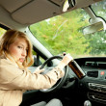 Smoking woman driving a car — Stock Photo
