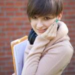 Female student near bricks wall — Stock Photo