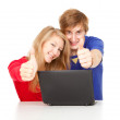 Couple with thumbs up using laptop — Stock Photo