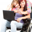 Invalid girl with laptop and friend — Stock Photo #7361913