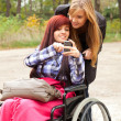 Invalid girl with friend - Stok fotoğraf
