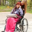 Invalid girl with friend - Stock Photo