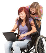 Invalid girl with laptop and friend — Stock Photo
