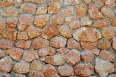 A wall of textured red stones. — Стоковое фото